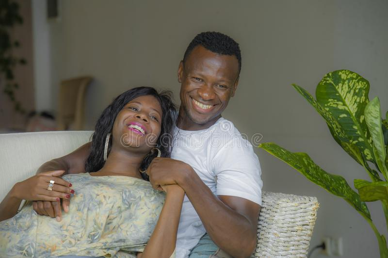 Young attractive and happy black African American couple relaxed at home sofa couch talking sweet enjoying together and smiling in. Men and women in love royalty free stock images