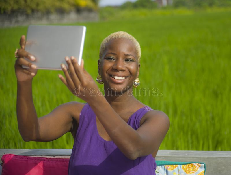 Young attractive and happy black african american woman outdoors taking selfie with digital tablet pad on green grass field backgr. Ound enjoying Summer holidays royalty free stock photography