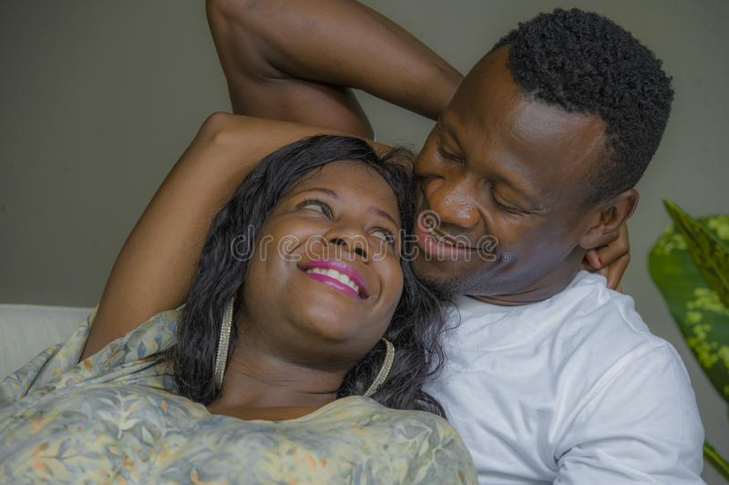 Young attractive and happy black afro American couple relaxed at home sofa couch cuddling sweet enjoying together and smiling in. Men and women in love enjoying royalty free stock images