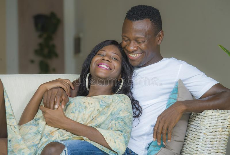 Young attractive and happy black afro American couple relaxed at home sofa couch cuddling sweet enjoying together and smiling in. Men and women in love enjoying royalty free stock image