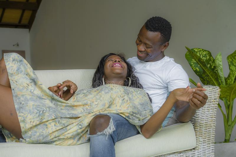 Young attractive and happy black afro American couple relaxed at home sofa couch cuddling sweet enjoying together and smiling in. Men and women in love enjoying stock photography
