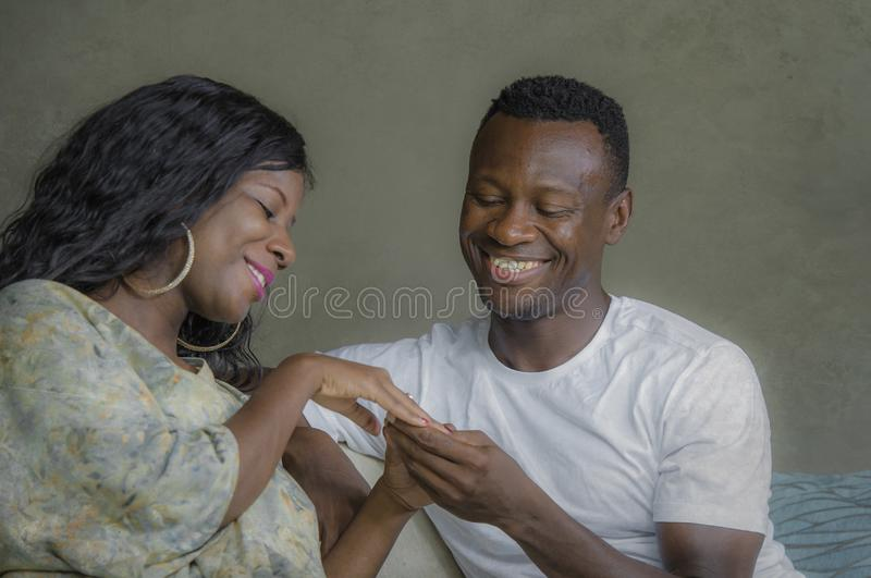 Young attractive and happy black afro American couple relaxed at home sofa couch talking sweet enjoying together and smiling in. Men and women in love enjoying stock images