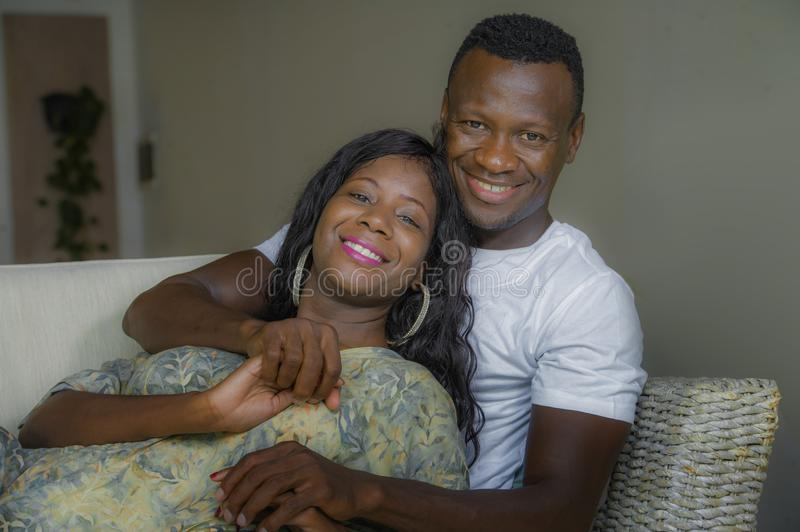 Young attractive and happy black afro American couple relaxed at home sofa couch talking sweet enjoying together and smiling in. Young attractive and happy black stock image