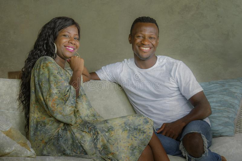 Young attractive and happy black afro American couple relaxed at home sofa couch talking sweet enjoying together and smiling in. Young attractive and happy black royalty free stock photo