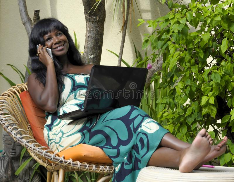 Happy black afro american woman in elegant dress working on luxury terrace villa with laptop talking on mobile phone. Young attractive and happy black afro royalty free stock images