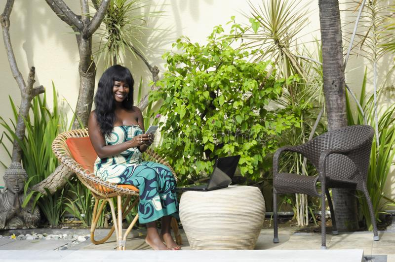 Happy black afro american woman in elegant dress working on luxury terrace villa with laptop and mobile phone. Young attractive and happy black afro american royalty free stock photos
