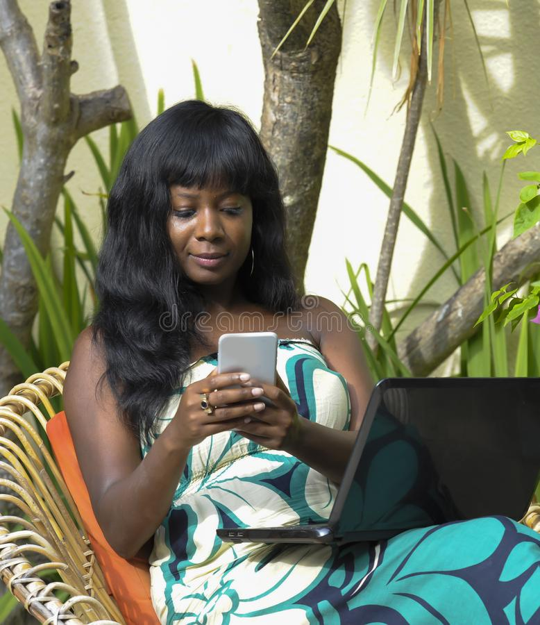 Happy black afro american woman in elegant dress working on luxury terrace villa with laptop and mobile phone. Young attractive and happy black afro american royalty free stock photo