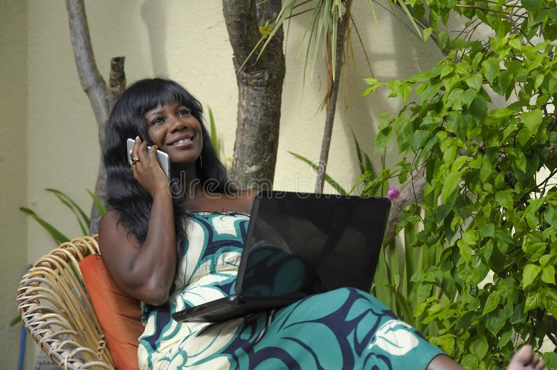 Happy black afro american woman in elegant dress working on luxury terrace villa with laptop talking on mobile phone. Young attractive and happy black afro royalty free stock photos