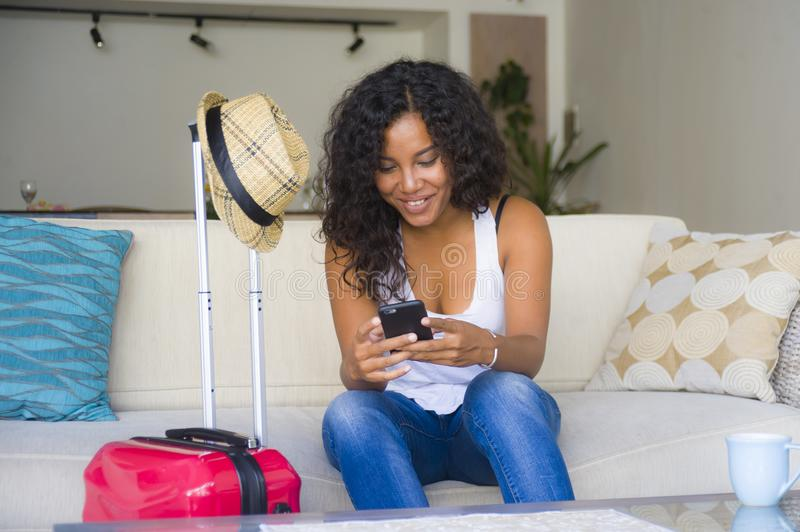 Young attractive and happy black afro American woman at home with suitcase using mobile phone leaving for holidays trip in tourism. Young attractive and happy royalty free stock image