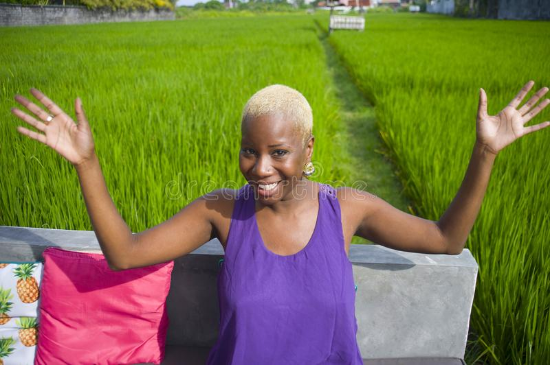 Young attractive and happy black afro american woman outdoors on green grass field background looking excited and playful enjoying. Summer holidays at tropical stock photo