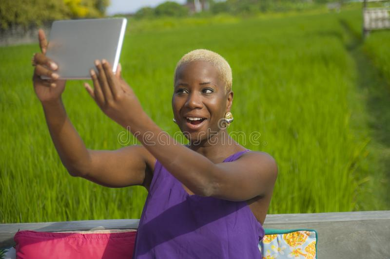 Young attractive and happy black afro american woman outdoors taking selfie with digital tablet pad on green grass field backgroun. D enjoying Summer holidays stock images