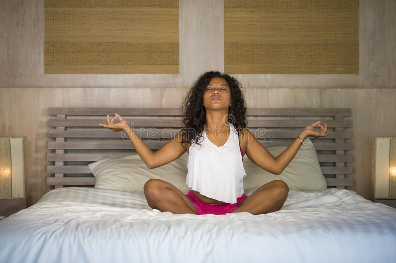 Young attractive and happy black hispanic woman at home bedroom doing yoga meditation and body relaxation exercise stretching on b stock photos