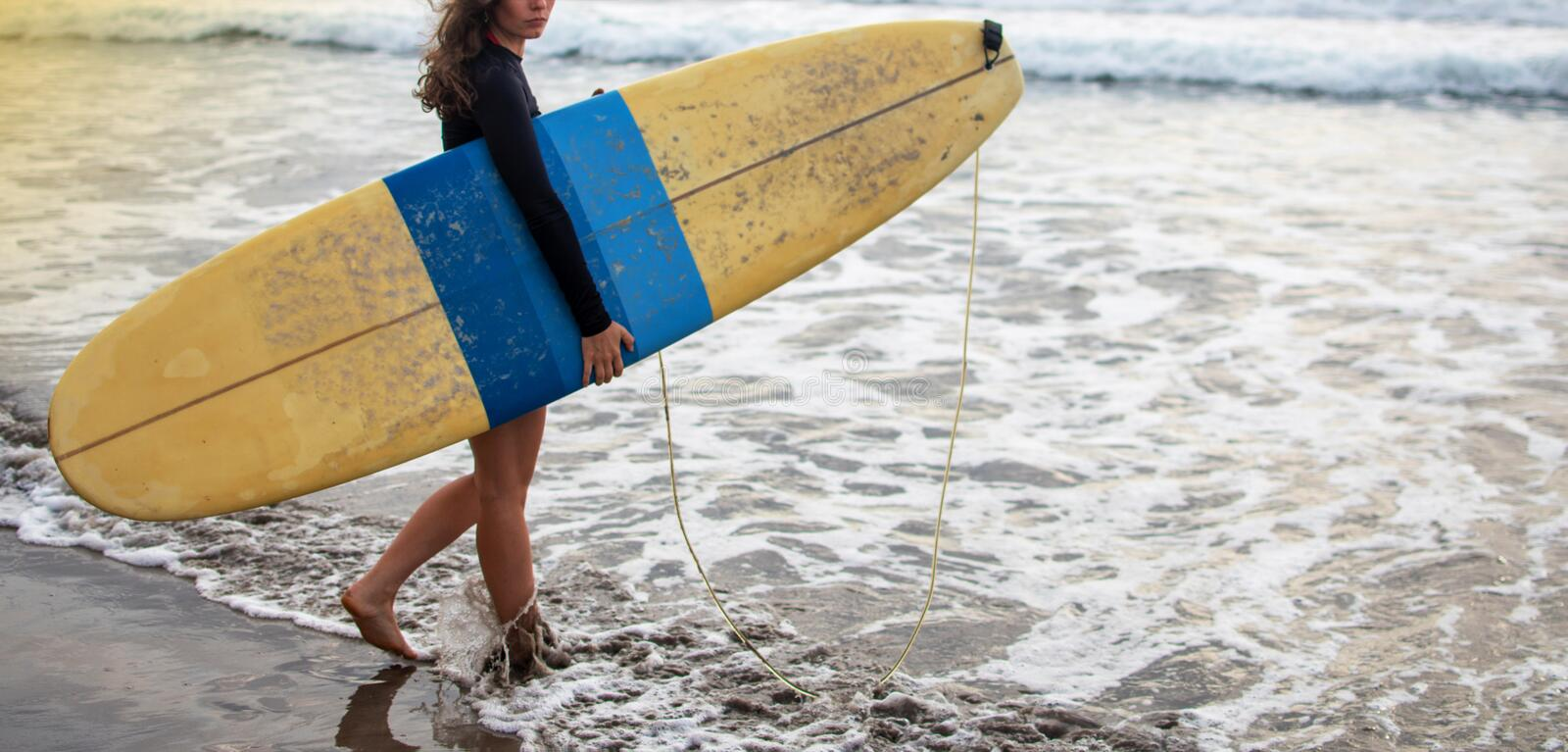Young attractive and happy surfer girl in beautiful beach carrying yellow surf board walking in the ocean enjoying stock photography