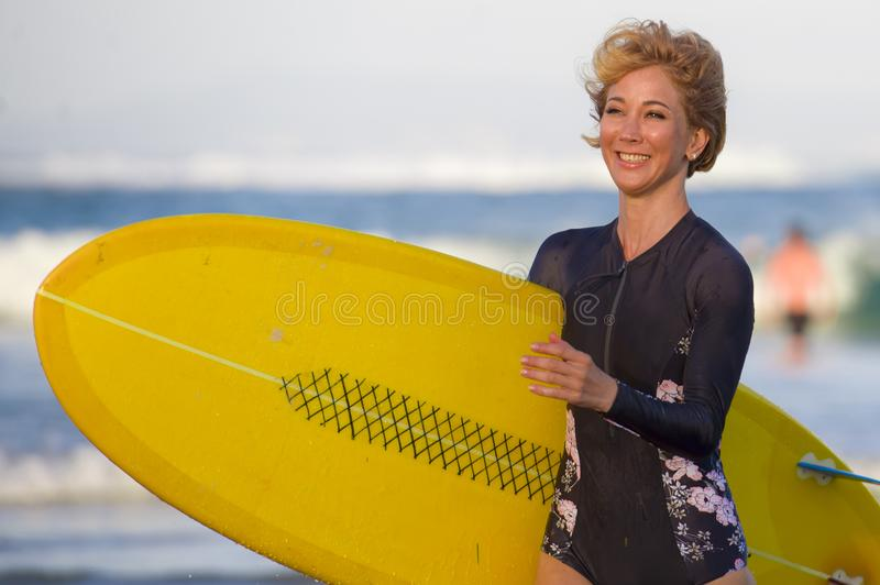 Young attractive and happy blonde surfer girl in beautiful beach carrying yellow surf board walking out of the water enjoying summ. Er holidays at tropical stock image