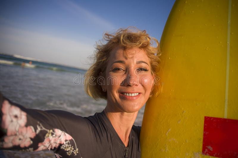 Young attractive and happy blonde surfer woman in swimsuit holding surf board in the beach taking self portrait selfie picture smi. Ling cheerful enjoying stock image
