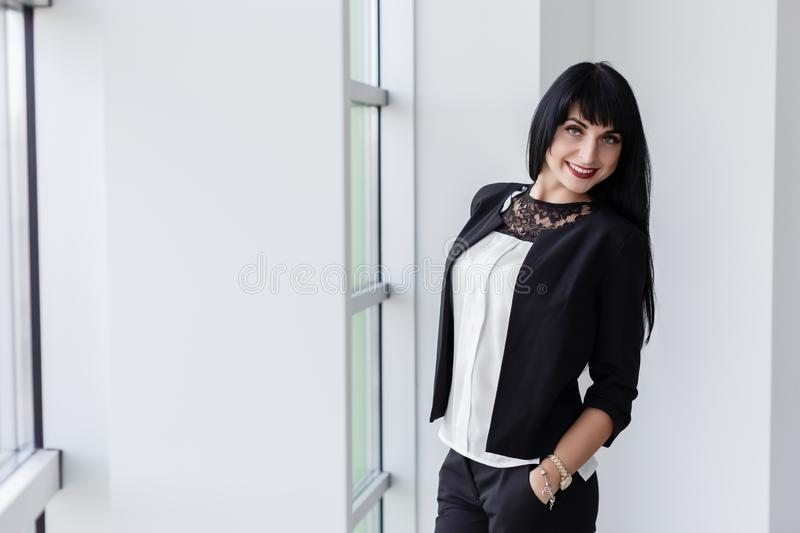 Young Attractive happy brunette woman dressed in a black business suit standing near the window in office, smiling, looking at royalty free stock photo