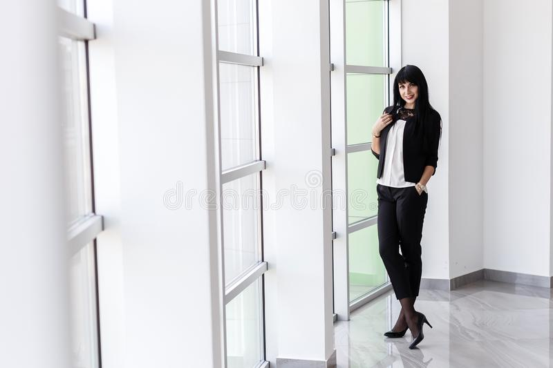 Young Attractive happy brunette woman dressed in a black business suit standing near the window in office, smiling, looking at royalty free stock photos