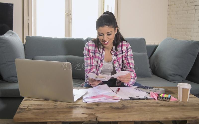 Young attractive and happy hispanic woman checking bills bank papers expenses and monthly payments smiling at apartment living roo. M couch in domestic finance royalty free stock photography