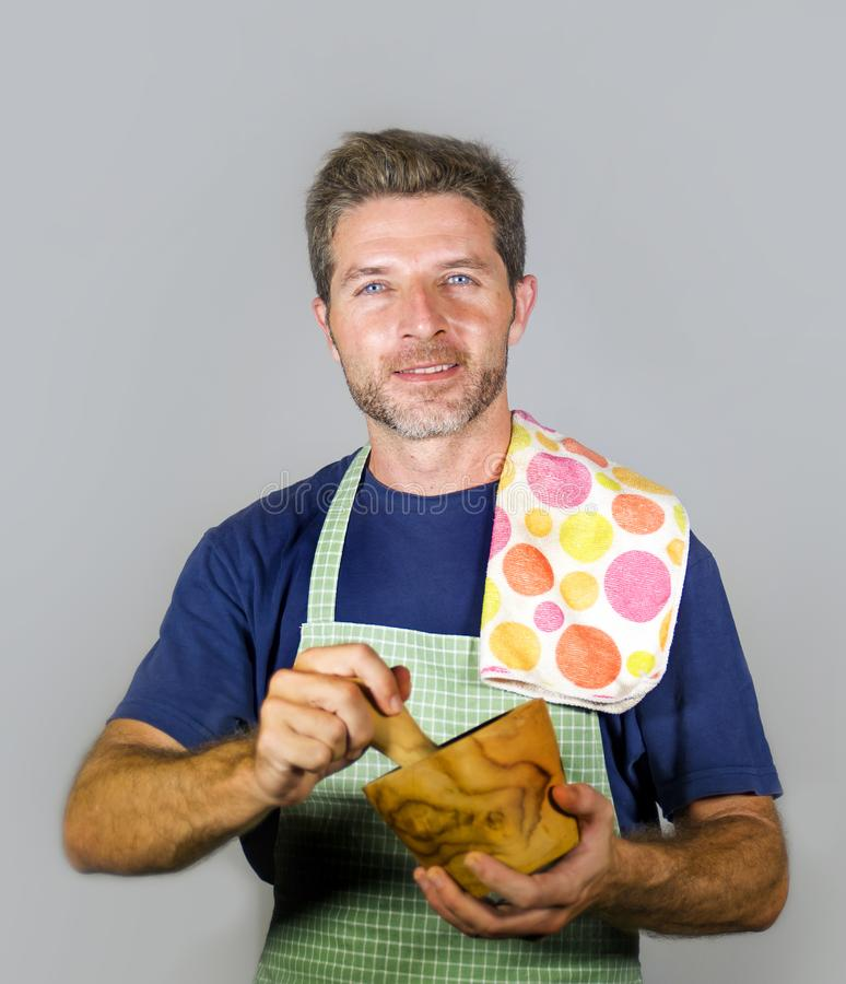 Young attractive and happy home cook man with apron and kitchen cloth grinding ingredient using mortar smiling satisfied and cheer stock photography