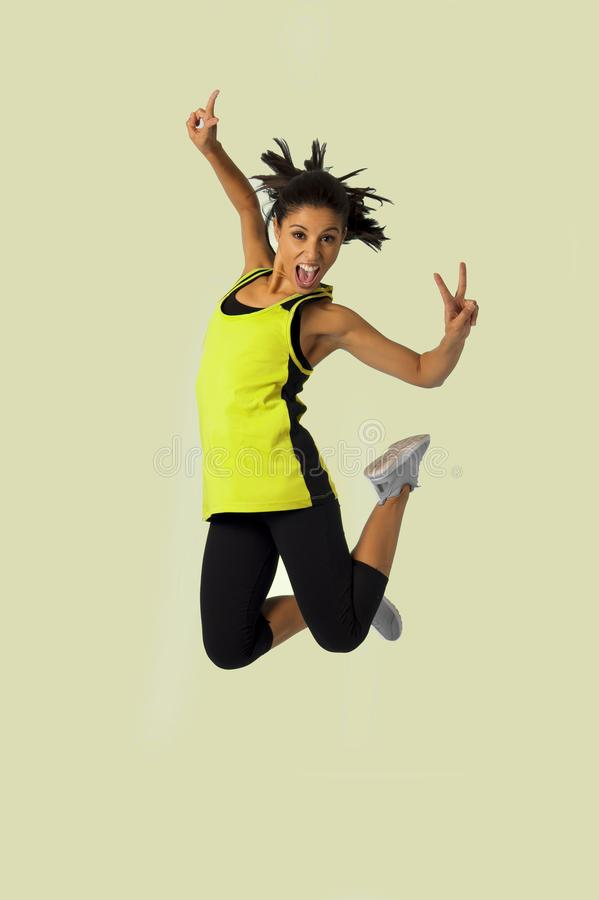 Young attractive and happy Latin sport woman jumping excited and cheerful in gym exercise workout healthy lifestyle and freedom co royalty free stock photos