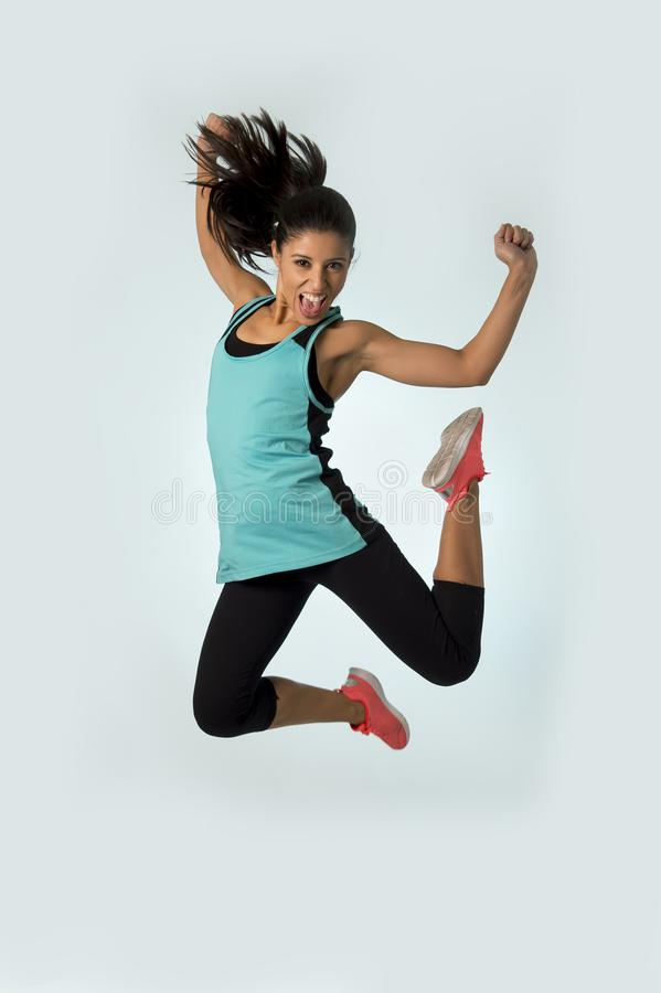 Young attractive and happy Latin sport woman jumping excited and cheerful in gym exercise workout healthy lifestyle stock image