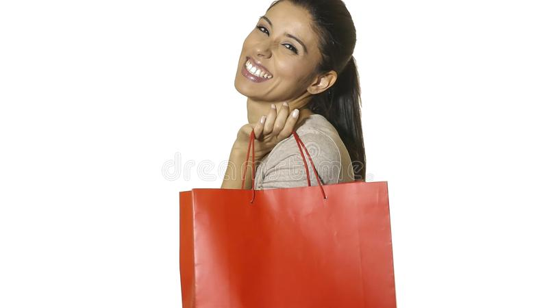 Young attractive and happy latin woman holding red shopping bag smiling cheerful and positive isolated on white background in sale. S and opportunities concept royalty free stock photo