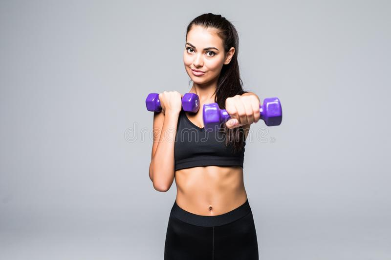 Young attractive woman in sport clothes with beautiful smile holding weight dumbbell doing fitness workout isolated on white backg stock photography