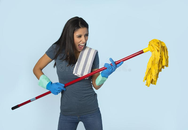 Young attractive happy Latin woman in washing gloves holding mop having fun singing and playing air guitar excited royalty free stock photos