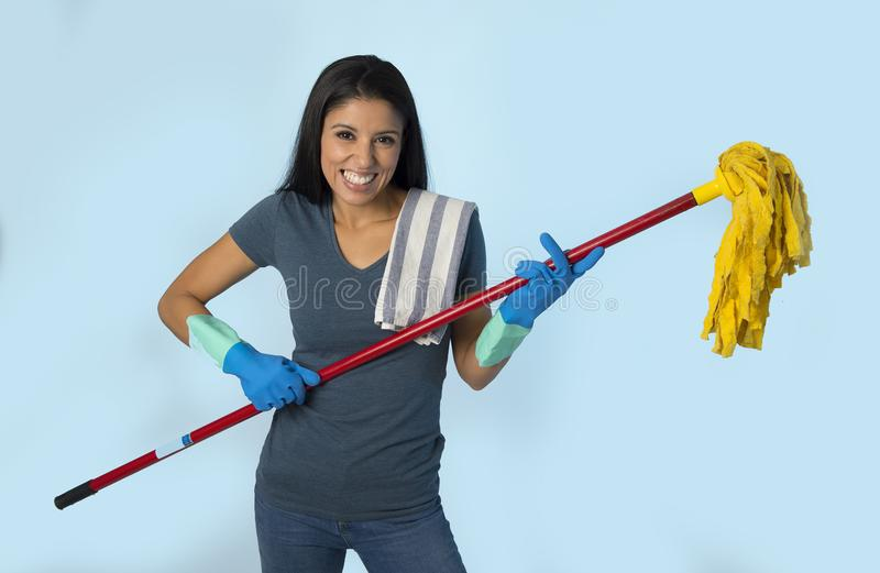 Young attractive happy Latin woman in washing gloves holding mop having fun singing and playing air guitar excited stock image