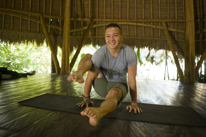 Young attractive and happy man doing yoga drill and acro exercise smiling relaxed in harmony at beautiful Asian bamboo hut stock photography