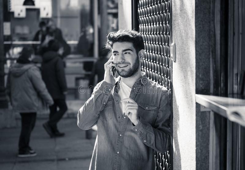 Young attractive happy man talking on smart phone in european city stock images