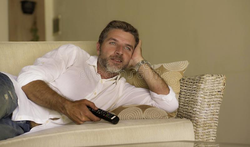 Young attractive and happy man watching television show or movie holding TV remote controller enjoying relaxed lying on living. Home lifestyle portrait of young royalty free stock photography