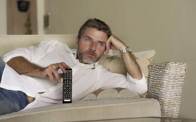 Young attractive and happy man watching television show or movie holding TV remote controller enjoying relaxed lying on living. Home lifestyle portrait of young royalty free stock images