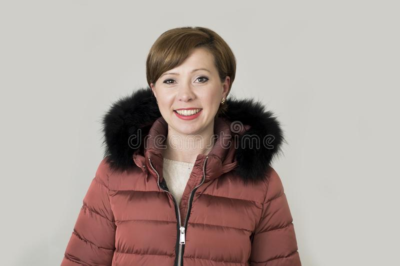 Young attractive and happy red hair Caucasian woman on her 20s o. R 30s posing cheerful and smiling wearing warm winter jacket with fur hood isolated on grey stock photo