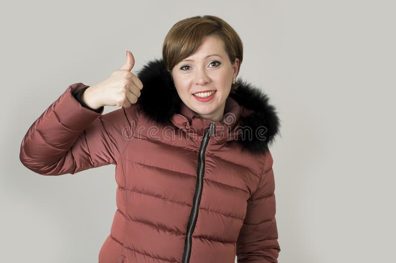 Young attractive and happy red hair Caucasian woman on her 20s o. R 30s posing cheerful and smiling wearing warm winter jacket with fur hood isolated giving stock photo