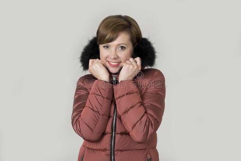 Young attractive and happy red hair Caucasian woman on her 20s o. R 30s posing cheerful and smiling wearing warm winter jacket with fur hood isolated on grey stock photography