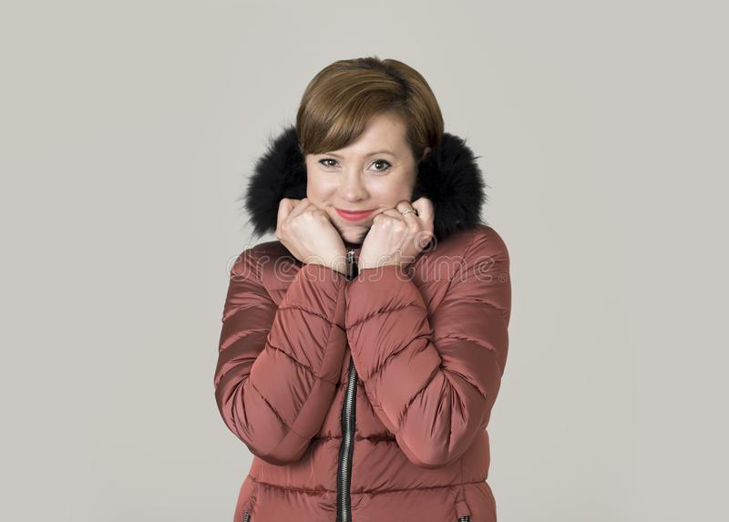 Young attractive and happy red hair Caucasian woman on her 20s o. R 30s posing cheerful and smiling wearing warm winter jacket with fur hood isolated on grey stock photos