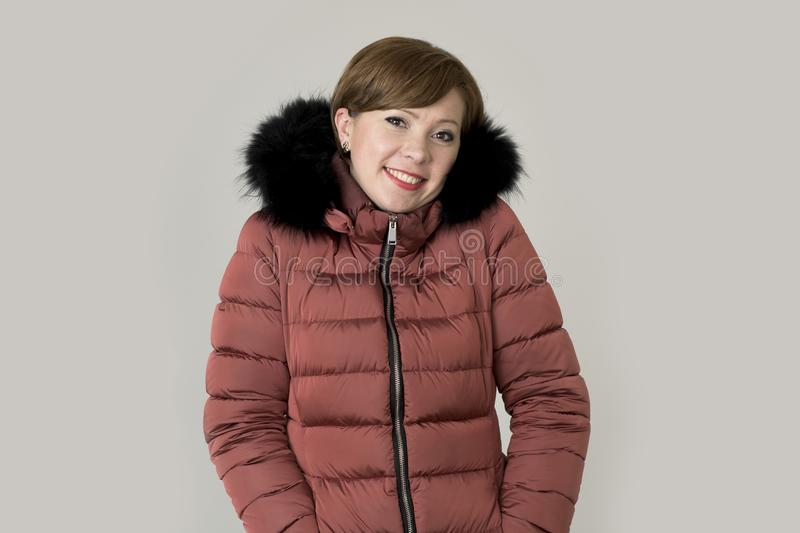 Young attractive and happy red hair Caucasian woman on her 20s o. R 30s posing cheerful and smiling wearing warm winter jacket with fur hood isolated on grey royalty free stock photos