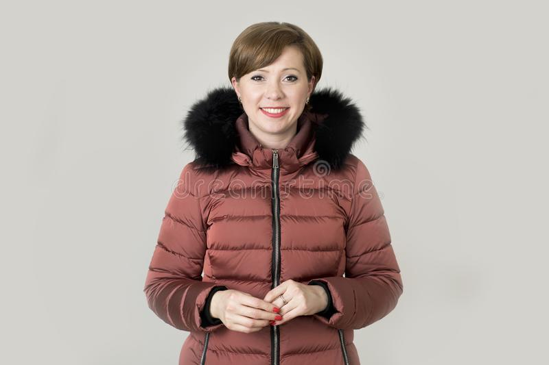 Young attractive and happy red hair Caucasian woman on her 20s o. R 30s posing cheerful and smiling wearing warm winter jacket with fur hood isolated on grey royalty free stock photography
