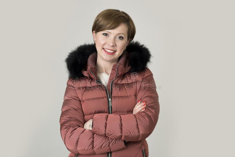 Young attractive and happy red hair Caucasian woman on her 20s o. R 30s posing cheerful and smiling wearing warm winter jacket with fur hood isolated on grey royalty free stock photo