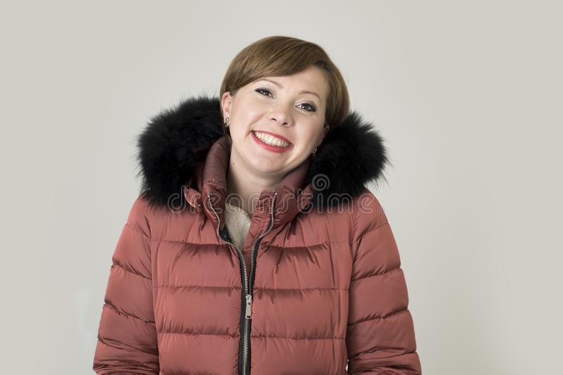 Young attractive and happy red hair Caucasian woman on her 20s o. R 30s posing cheerful and smiling wearing warm winter jacket with fur hood isolated on grey royalty free stock images