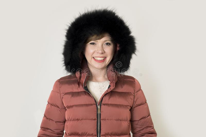 Young attractive and happy red hair Caucasian woman on her 20s or 30s posing cheerful and smiling wearing warm winter jacket. And fur hood isolated on grey royalty free stock image