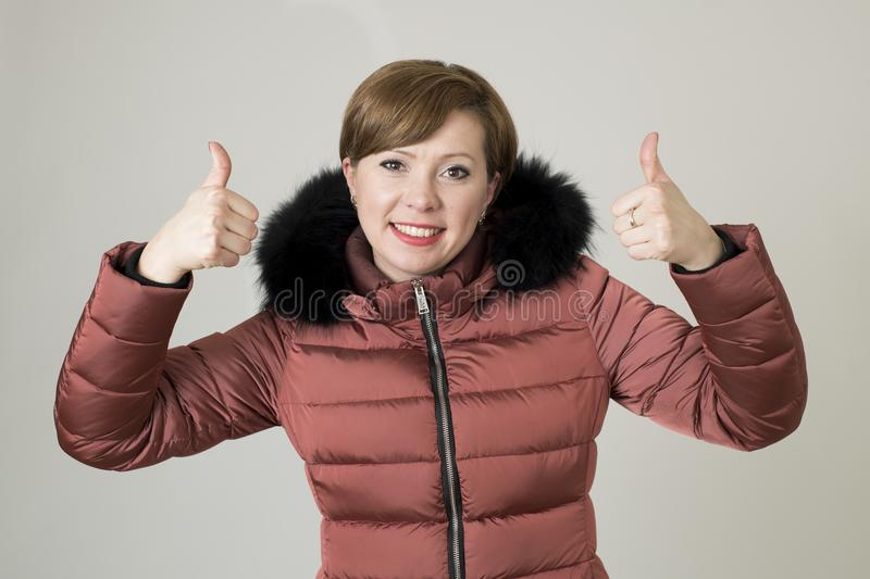 Young attractive and happy red hair Caucasian woman on her 20s or 30s posing cheerful and smiling wearing warm winter jacket with. Fur hood isolated giving royalty free stock image