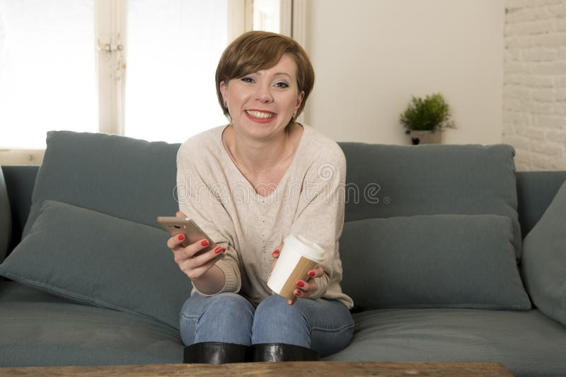 Young attractive and happy red hair woman sitting at home sofa c. Ouch drinking coffee using internet dating app on mobile phone relaxed in communication and stock photo
