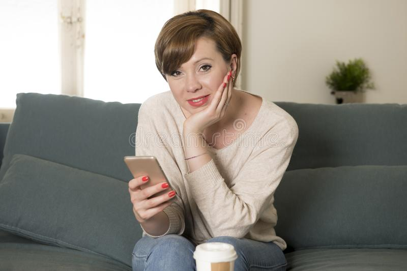 Young attractive and happy red hair woman sitting at home sofa c. Ouch drinking coffee using internet dating app on mobile phone relaxed in communication and royalty free stock photos