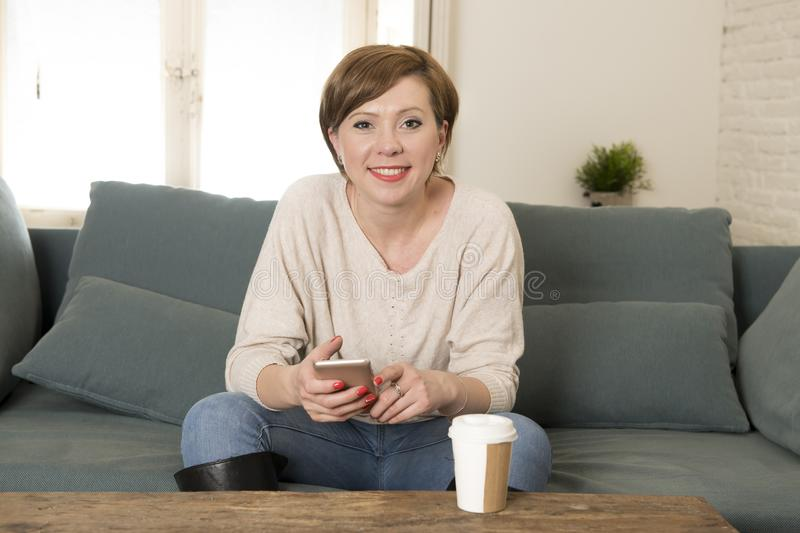 Young attractive and happy red hair woman sitting at home sofa c. Ouch drinking coffee using internet dating app on mobile phone relaxed in communication and stock images