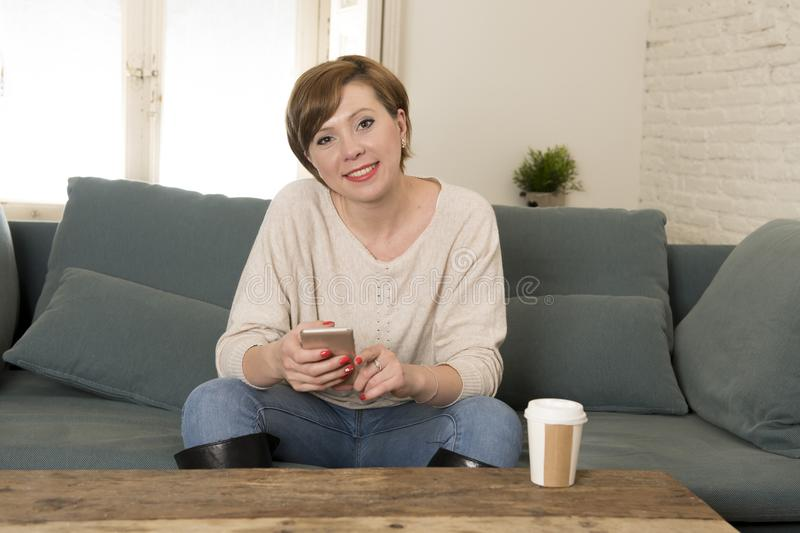 Young attractive and happy red hair woman sitting at home sofa c. Ouch drinking coffee using internet dating app on mobile phone relaxed in communication and royalty free stock images