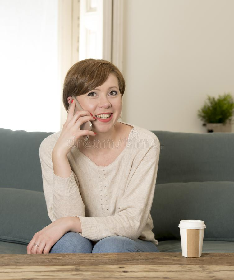 Young attractive and happy red hair woman sitting at home sofa c. Ouch drinking coffee talking on mobile phone relaxed in communication and lifestyle concept royalty free stock photo