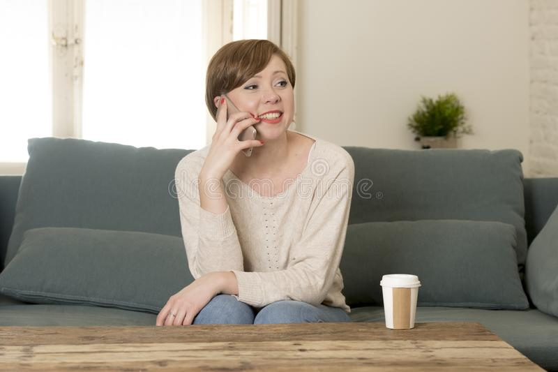 Young attractive and happy red hair woman sitting at home sofa c. Ouch drinking coffee talking on mobile phone relaxed in communication and lifestyle concept stock photography