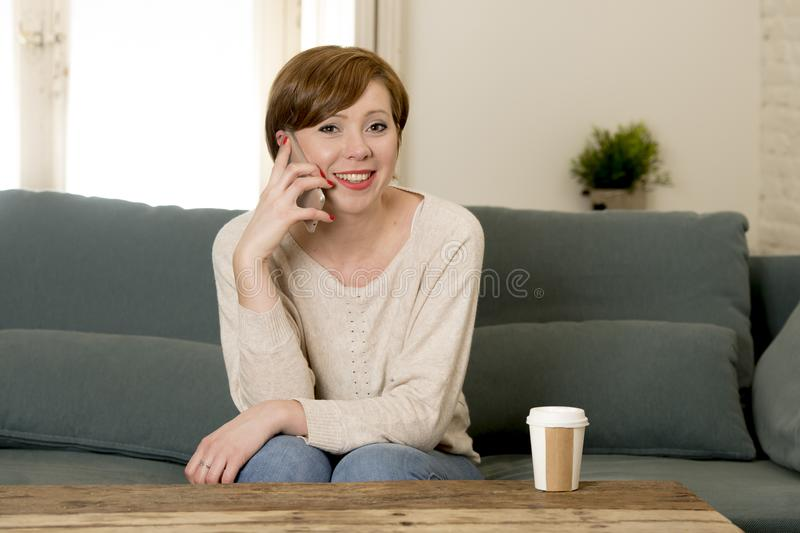 Young attractive and happy red hair woman sitting at home sofa c. Ouch drinking coffee talking on mobile phone relaxed in communication and lifestyle concept royalty free stock images